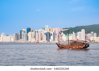 Hong Kong - July 16, 2019 : A tourist sailboat sailing in Victoria harbor with out of focus modern buildings on Hong Kong Island background.
