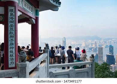Hong Kong - July 16, 2019 : Tourists sightseeing and taking photos of Hong Kong skyline at Victoria Peak in Hong Kong.