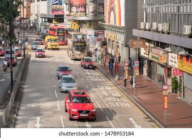 Hong Kong - July 16, 2019 : Taxi cabs, Double dacker buses, and provate cars running on Tsim Sha Tsui road. Hong Kong transportation.