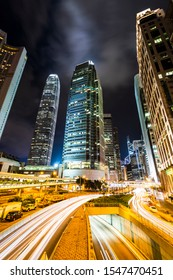 Hong Kong -July 23, 2019: Street traffic in Hong Kong at night. Office skyscraper buildings and busy traffic on highway road with blurred car light trails. Hong Kong.