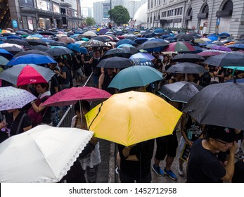HONG KONG - JULY 7 2019: HK people carrying iconic umbrellas marching along the  Nathan Road against the controversial Extradition Bills that allow govt to send people to mainland China for trial.