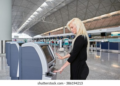 HONG KONG - JUNE 02, 2015: blonde woman using self check-in kiosk. Self Check-in service offers the opportunity to save time avoiding the check-in counter queues