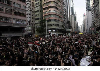 HONG KONG - JUNE 16 2019: a sea of black with an iconic yellow umbrella. Hong Kong people protesting against the controversial Extradition Bills that allows people to be sent to China for trial