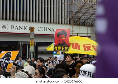 HONG KONG - JUNE 9, 2019: Protesters pass a Chinese state-owned bank. Thousands of protesters marched against a controversial extradition bill.