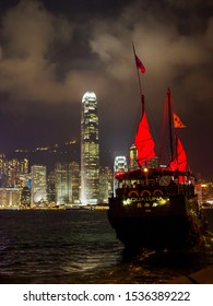 Hong Kong, Kowloon - November 10, 2014: Hong Kong night view with iconic junk ship in foreground with illuminated International Finance Centre rising high above the skyline
