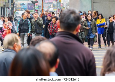 Hong Kong, Hong Kong - March 10, 2017: crowds of unidentified people crossing a road in Hong Kong. HK is one of worlds most significant financial centres and the 4th most densely populated state
