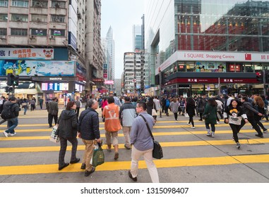 HONG KONG - MARCH 16, 2017: People cross a road by the iSquare shopping centre downtown the city. The tourism industry is an important part of the economy of Hong Kong.