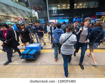 HONG KONG - MARCH 2017: Pedestrians cross Des Voeux Road Central bya Louis Vuitton store in Central. The tourism industry is an important part of the economy of Hong Kong.