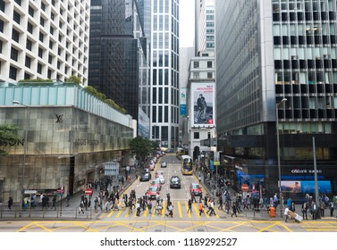 HONG KONG - MARCH 2017: Pedestrians cross Pedder Street by a Louis Vuitton store in Central. The tourism industry is an important part of the economy of Hong Kong.
