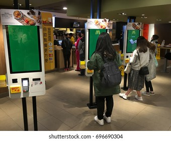 HONG KONG - MARCH, 2017: People order food at self service kiosks at a McDonalds in Peking Road. McDonalds franchisees start to worry about rising labor costs and the technology will help reduce them.