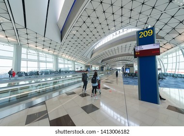 HONG KONG - MARCH 21, 2017: Unidentified people walk in the Hong Kong International Airport departure area. It is the main airport in Hong Kong located on the island of Chek Lap Kok