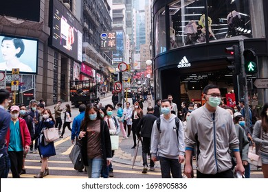 Hong Kong - March 21, 2020: Street view in Central district. People walking on the street and wearing mask to protect corona virus spread in air. Central area is main commercial district of Hong Kong