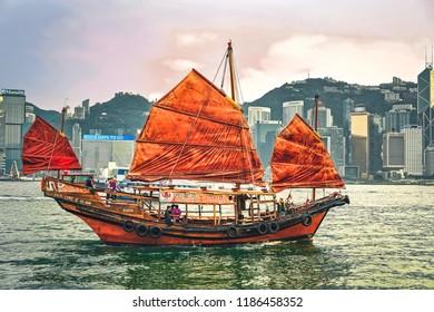 Hong Kong, Hong Kong - March 6, 2016: Junk boat at Victoria Harbor in Hong Kong at sunset. View from Kowloon on HK Island.