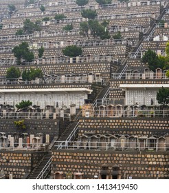 Hong Kong - March 9, 2019 - Stairway on a hillside of numerous tombstones in a crowded Hong Kong cemetery
