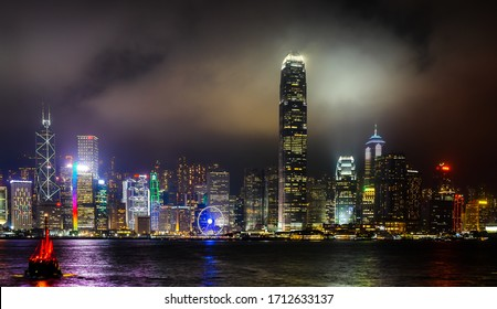 Hong Kong, May 19th 2016. Victoria harbour at night, looking across to Central on Hong Kong Island. Traditional tourist junk boat.