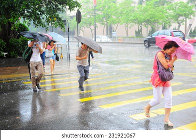 HONG KONG - MAY 20, 2013: People crossing the road in the rain.  With a land mass of 1,104 km and population of 7 million people, Hong Kong is one of the most densely populated areas in the world