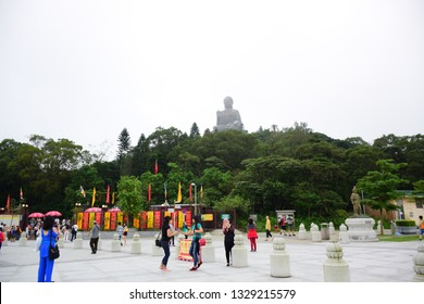 HONG KONG - MAY 31 2018: Tourists spending their time at the Po Lin Monastery with Tian Tan Buddha statue up on the hill in background, Ngong Ping Village, Lantau Island, Hong Kong