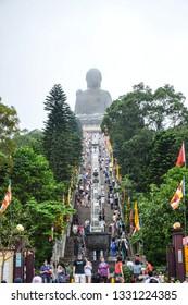 HONG KONG - MAY 31 2018: Tourists travelling to worship Tian Tan Buddha big statue up on the hill next to Po Lin Monastery in Ngong Ping Village, Lantau Island, Hong Kong