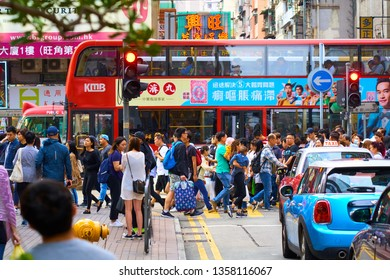 HONG KONG - OCTOBER 13, 2018: Pedestrians and cars on the crosswalk in downtown of famous Asian city.