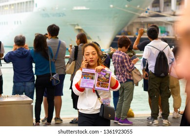 HONG KONG - OCTOBER 14, 2018: Spa salon leaflet distributor is standing in front of the tourists make photo of beautiful sunset on the quay of Victoria harbour.