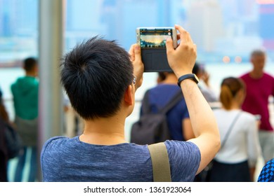 HONG KONG - OCTOBER 14, 2018: Tourists make photo of beautiful sunset on the quay of Victoria harbour.