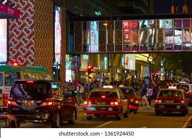 HONG KONG - OCTOBER 14, 2018: Taxi cars drive on the night road of the Asian metropolis.