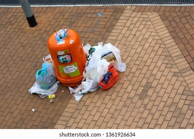 HONG KONG - OCTOBER 14, 2018: Plastic bags with trash near overloaded trash can.