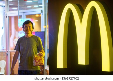 HONG KONG - OCTOBER 14, 2018: Happy european male tourist with paper bag in the hand get out from McDonald's restaurant on the street of Asian metropolis at night time.