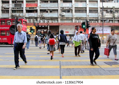 HONG KONG OCTOBER 2011 - Chinese are crossing on the street during early morning in Fortress Hill district