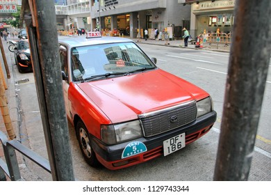 HONG KONG OCTOBER 2011 - Taxi's driver is parking his res taxi car in the street while he go out for lunch