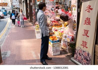 HONG KONG - OCTOBER 22, 2017_Unidentified man shopping fruits at a grocery shop in Sheung Wan, Hong Kong. Sheung Wan is an area in Hong Kong, located in the north-west of Hong Kong Island