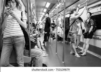 HONG KONG - OCTOBER 22, 2017_Unidentified passenger browsing smartphone in Hong Kong subway system at rush hour, shallow depth of field, black and white photography