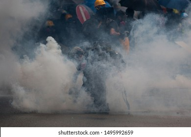 Hong Kong protestor picking up a tear gas cannister