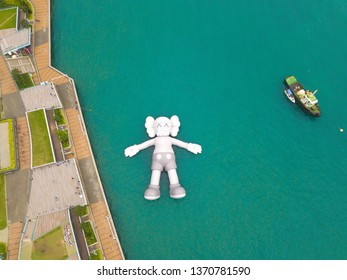 Hong Kong/ Republic of China - 04/16/2019 : Aerial view of KAWS companion, giant sculpture floating on water. Figure in Victoria Harbour.