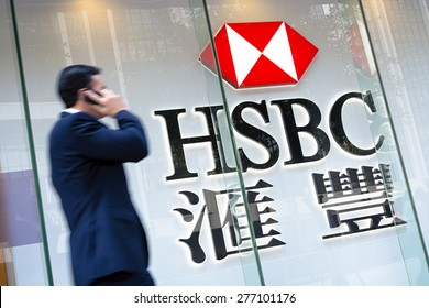 Hong Kong, Hong Kong SAR -November 17, 2014: Motion blured business man passing by an HSBC Bank sign in Hong Kong. HSBC Holdings plc  is the world's third largest bank by assets.