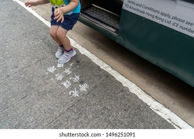 """Hong Kong - Sep 03, 2019: Hong Kong Water Revolution, Chinese wordings on road cross written as """"Liberate Hong Kong; The Revolution of Our Times"""" near at the tram station. Kid jumping of the tram."""
