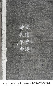 """Hong Kong - Sep 03, 2019: Hong Kong Water Revolution-Chinese wordings on road cross written as """"Liberate Hong Kong; The Revolution of Our Times"""" near at the tram station."""