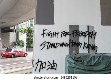 """Hong Kong - Sep 03, 2019: Hong Kong Water Revolution - Wordings on wall """"Fight for freedom; Stand with Hong Kong"""" and """"Add Oil"""" in Chinese. Hong Kong Taxi as background."""