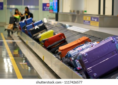 HONG KONG - September 1, 2017: Row of suitcases on baggage claim conveyor carousel at Hong Kong airport. Out of focus travelers with luggage trolley in background.