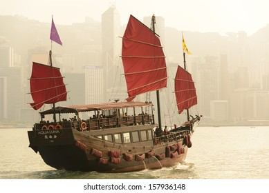 HONG KONG - SEPTEMBER 15: Victoria Harbor on September 15, 2013 in Hong Kong. An old Chinese junk departed from Ocean Terminal and drove across Victoria Harbor during sunset.