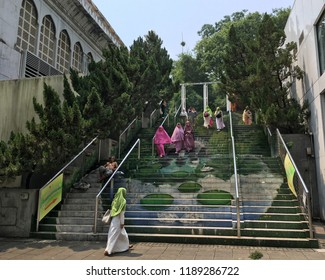 HONG KONG - SEPTEMBER 17, 2017: Muslim women go up and down the stairs by Kowloon Masjid and Islamic Centre.