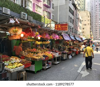 HONG KONG - SEPTEMBER 19, 2017: People walk by a line of small fruit and food shops of an outdoor wet market in Mong Kok district.