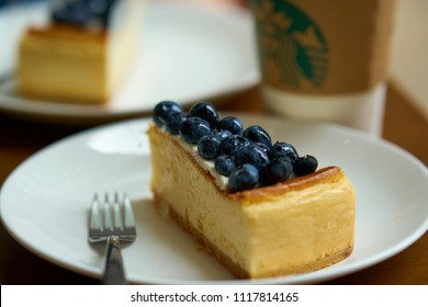 HONG KONG - September 2, 2017: Delicious blueberry dessert cheesecake on plate and cup of coffee in Starbucks coffee shop. Illustrative editorial.