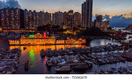 HONG KONG - SEPTEMBER 29 2017: A boat moving away from the floating restaurant on Aberdeen Harbour at night with external lighting. Editorial Use Only.