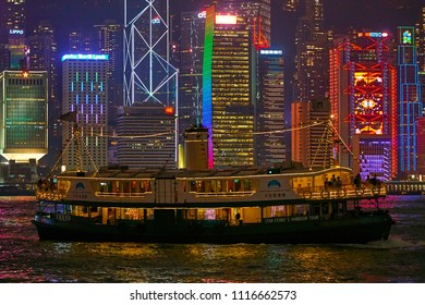 HONG KONG - September 3, 2017: Tourists watching Symphony of Lights show from deck of sightseeing ferry in multi color reflection water of Victoria Harbor with illuminated skyscrapers in background
