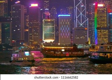 HONG KONG - September 3, 2017: Boats and old fashioned ferries in multi color reflection water of Victoria Harbor with illuminated skyscrapers during A Symphony of Lights show.