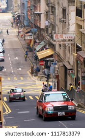 HONG KONG - September 3, 2017: Red taxi cab driving on sloping road. Street scene in Hong Kong