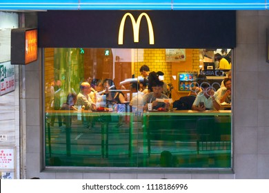 HONG KONG - September 4, 2017: Street traffic reflecting in glass window of McDonald's fast food restaurant. Scene of daily life in Asian Metropolis. Illustrative editorial.