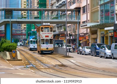HONG KONG - September 5, 2017: Street scene of double decker tram moving under elevated walkway along high rise residential building. Public Transport in Hong Kong.