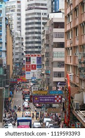 HONG KONG - September 5, 2017: Big advertising banners over the people and cars on the overcrowded street of the big city.